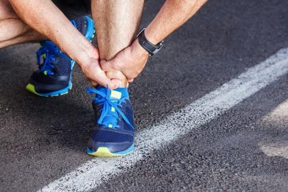 Achilles tendonitis - running sport injury. Male runner touching leg