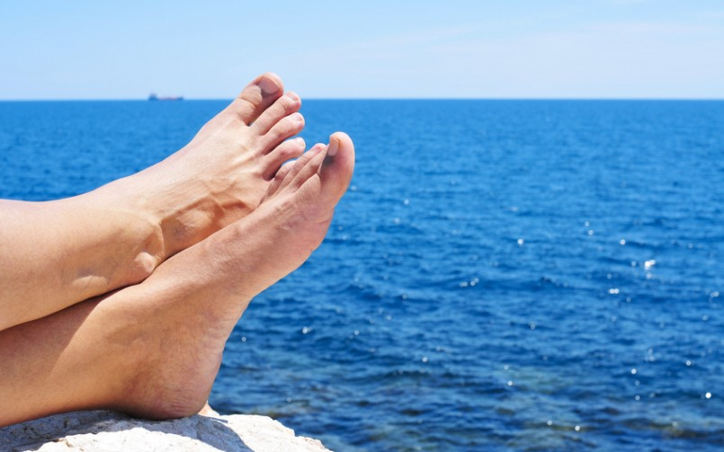 bare feet of a man who is relaxing near the ocean in the summer without hammertoes